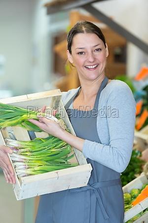 laechelnde verkaeuferin auf dem gemuesemarkt