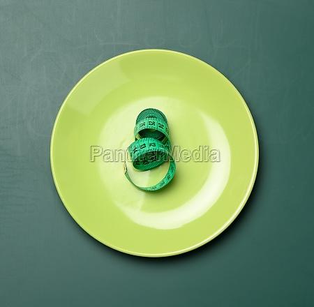 gruene rundplatte und gruenes massband auf