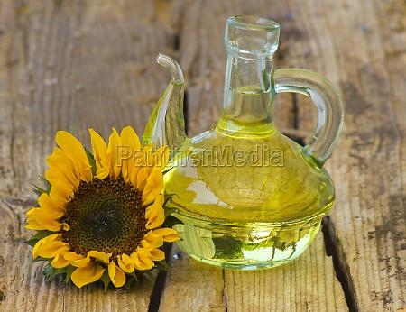 glasflasche mit sonnenblumenoel und sonnenblume auf
