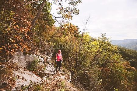 wanderfrau mit rucksack wandern auf waldweg