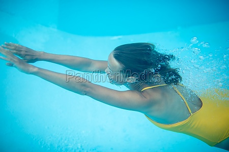 wunderschoene junge frau in einem pool