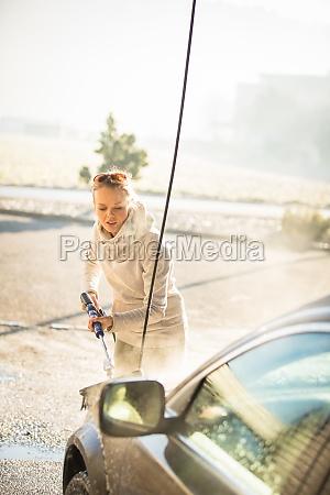 huebsche junge frau waschen ihr auto