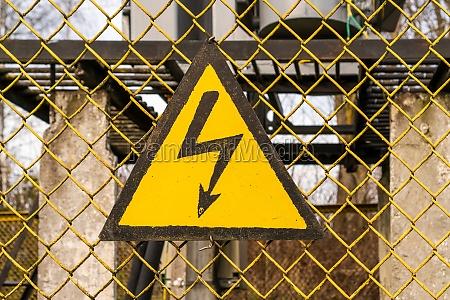 gelbes warnschild am zaun des umspannwerks