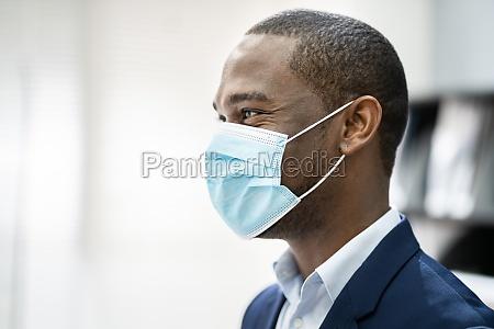 rezeptionist mann traegt medizinische maske