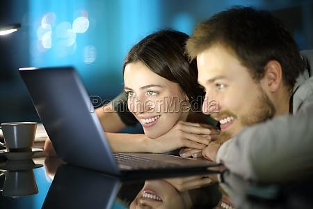 glueckliches paar beobachten medien auf laptop