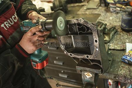 mechaniker reinigt das ersatzteil