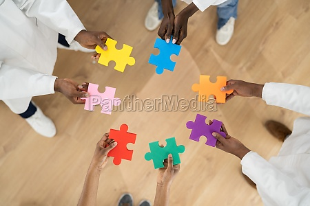 african medical doctor group holding puzzle