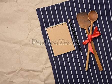 blaue kochschuerze holzloeffel und notizbuch mit