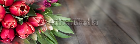 rote tulpen auf dunklem rustikalem holz
