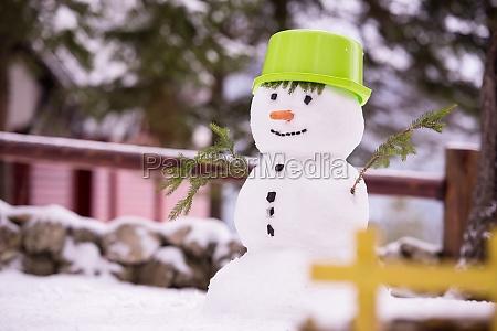 laechelnder schneemann mit gruenem hut