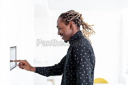 afrikanischer mann mit smart home bildschirm