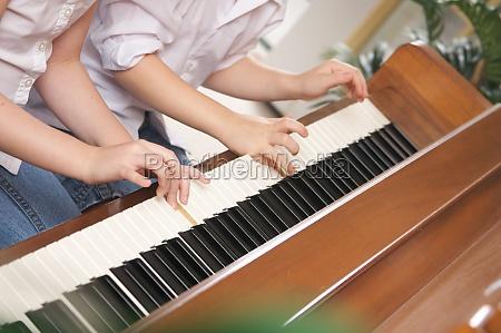 bruder und schwester spielen gemeinsam klavier