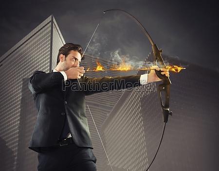 determinierter geschaeftsmann mit flammendem pfeil nimmt