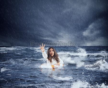 geschaeftsfrau im ozean mit rettungsgurt bittet