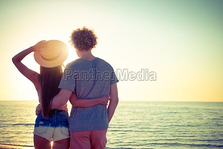 junge paare bei sonnenaufgang am strand