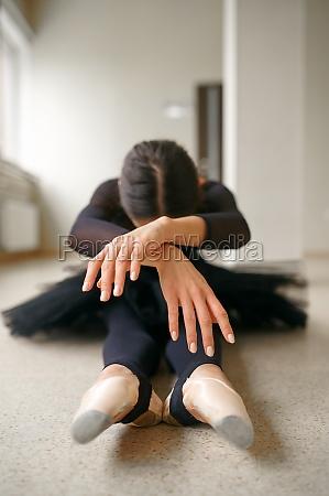 ballerina sitzt auf dem boden in