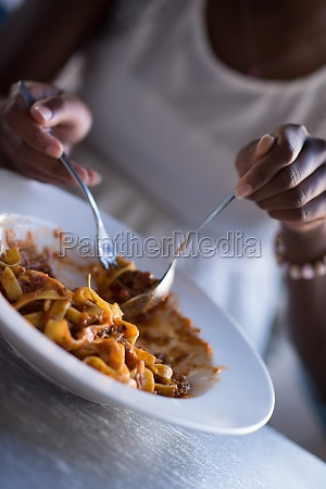 eine junge afroamerikanerin die nudeln isst