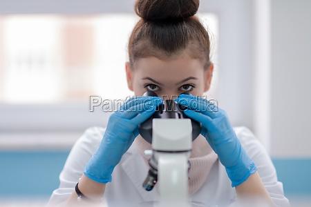 studentin beim blick durch ein mikroskop