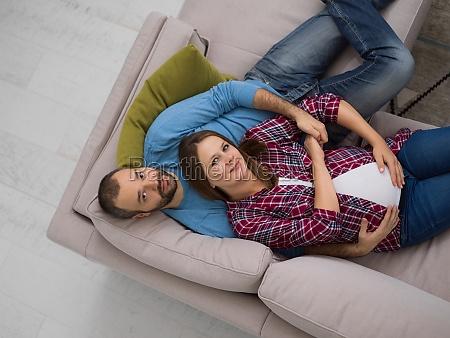 schwangeres paar entspannend auf dem sofa