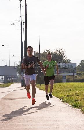 athletische junge maenner geniessen das laufen