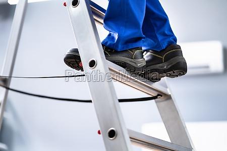 mann in schuhen klettern schritt leiter