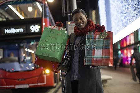 portraet glueckliche junge frau mit weihnachtsgeschenken