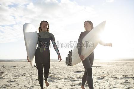 froehliche junge surferinnen laufen mit surfbrettern