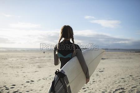 junge surferin mit zoepfen und surfbrett