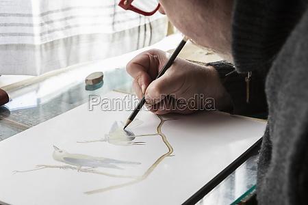 reifer kuenstler bei der arbeit zeichnen